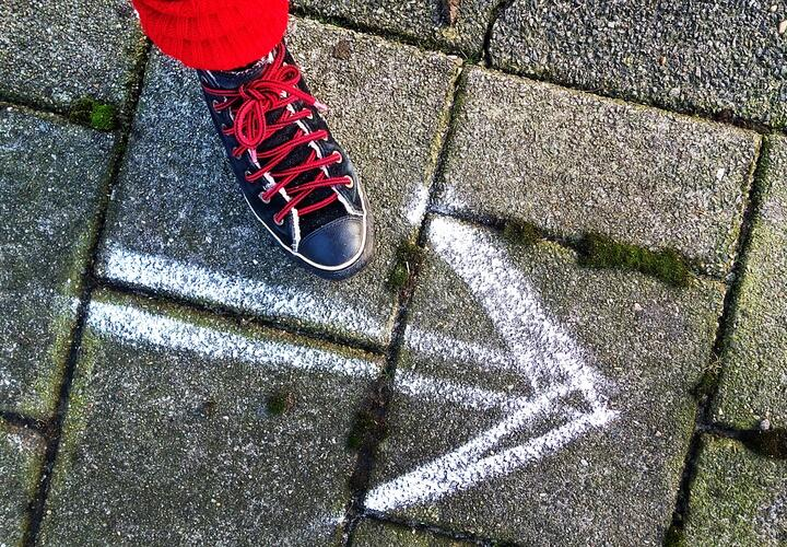 Shoe with arrow in chalk on road