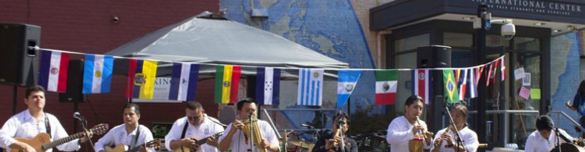 Band playing in front of a hanging line of assorted country flags