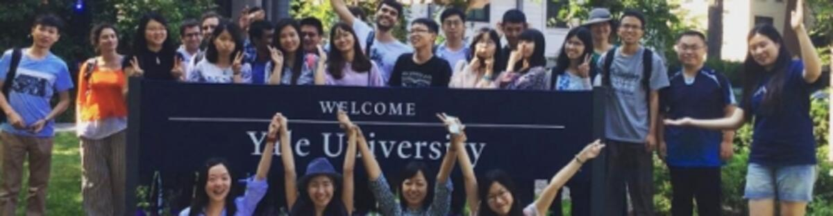 Group of International students and scholars next to a Yale sign