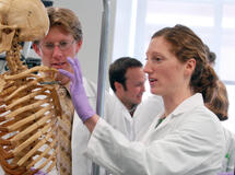 Woman with a skeleton in a medical setting